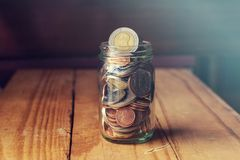 Coins in glass jar on wood table, Saving money concept. royalty free stock photos