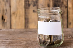 Coins in a glass jar on wooden table Royalty Free Stock Image