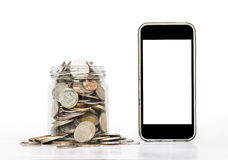 Coins in glass with mobile phone, on white background Stock Photography