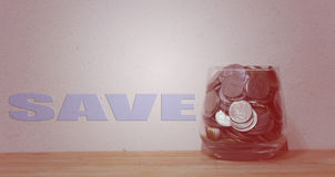 Coins in glass money jar  with a backdrop of old wall that says Royalty Free Stock Photo