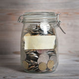 Coins in glass money jar with blank label Stock Photo