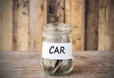 Coins in glass money jar with car label, financial concept. Royalty Free Stock Images