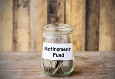Coins in glass money jar with Retirement fund label Stock Images