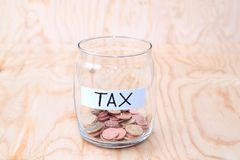 Coins in glass money jar with tax label, financial concept. Vintage wooden background Royalty Free Stock Images