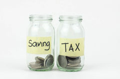 Coins in glass money jar with tax and savings label Stock Images