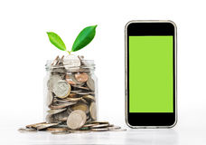 Coins in glass with plant and smart phone with blank copy space on screen, isolated on white background Royalty Free Stock Images