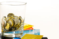 Coins glass and credit cards. Coins in glass on top of credits cards. No more credit cards, use cash Royalty Free Stock Photography