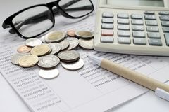 Coins, glasses, calculator and pen on savings account passbook Stock Photo