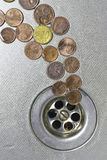 Coins go to drain Stock Image
