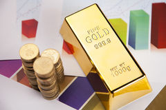 Coins and gold bar on chart. Gold, money and financial concept closeup in studio royalty free stock image