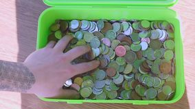 Coins in green box. Coins in a green box, hand touches coins stock footage