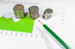 Coins on green graphs and charts background with pencil. money a Stock Images