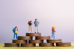 Coins and group of traveler miniature mini figures with backpack stand and walking on passport. royalty free stock image