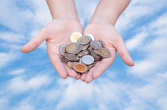 Coins in hands on blue sky. Donation Investment Fund Financial Support Charity  Dividend Market Growth Home House Stock Trust Wealthy Giving Planned Accounting Stock Photos