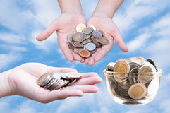 Coins in hands on blue sky. Donation Investment Fund Financial Support Charity  Dividend Market Growth Home House Stock Trust Wealthy Giving Planned Accounting Royalty Free Stock Image