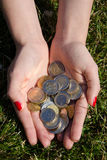 Coins in the hands of a girl against the grass. Money in the hands of a girl Royalty Free Stock Photo