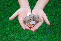 Coins in hands on grass. Donation Investment Fund Financial Support Charity  Dividend Market Growth Home House Stock Trust Wealthy Giving Planned Accounting Royalty Free Stock Photography