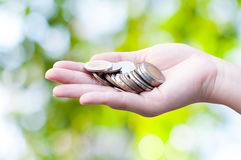 Coins in hands on green nature background. Donation Investment Fund Financial Support Charity  Dividend Market Growth Stock Photos