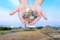 Coins in hands on Industry Landscape background. Donation Investment Fund Financial Support Charity  Dividend Market  Wealthy Giving Planned Accounting Royalty Free Stock Images