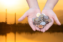 Coins in hands on Industry  silhouette Landscape background Stock Image