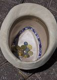 Coins in a hat. A hat of a beggar placed on the ground with coins in it Royalty Free Stock Images