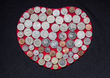 Coins on Heart. Lots of Coins on Red Heart - Black Background Royalty Free Stock Image