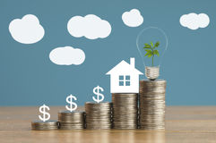 Coins and house paper with green small tree, light bulb on money, concept in save, finance and grow of business about home. Pile of coins and house paper with Stock Image