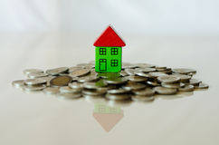 Coins and house standing on it Stock Images