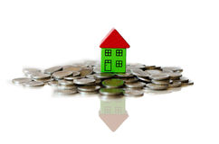 Coins and house standing on it Royalty Free Stock Images