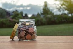 Free Coins In Glass Jar For Money Saving Financial Concept.Saving Money For Investing And For The Future Stock Photos - 192939533