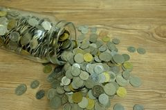 Coins abundant out from jar. Coins inside of glass jar and abundant out from a cookie jar mouth in wood background Royalty Free Stock Photos