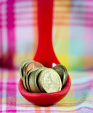 Coins inside red spoon put on table Stock Photos