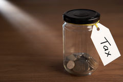 Coins in a jam jar. With tax label Royalty Free Stock Photos