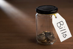 Coins in a jam jar. With label saying bills Stock Photo