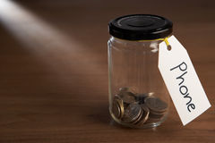 Coins in a jam jar. With phone label Royalty Free Stock Photo