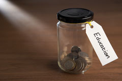 Coins in a jam jar. With education label Stock Photo