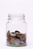 Coins in the jar. On white background Royalty Free Stock Photos