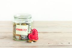 Coins in jar with Charity text. Coins in glass jar with Charity label. Money savings, charity and donation concept, copy space Stock Images