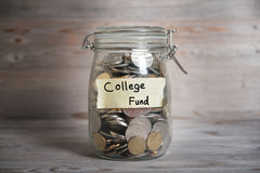 Coins in jar with college fund label. Coins in glass jar with college fund label, financial concept. Vintage wooden background with dramatic light Stock Photo