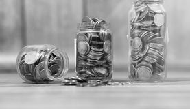 Coins in a jar on the floor. Accumulated coins on the floor. Sav. Coins in a jar on the floor. Accumulated coins on the floor. Pocket savings in piles.r Stock Photo