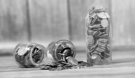 Coins in a jar on the floor. Accumulated coins on the floor. Sav Stock Image