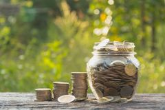 Coins in jar with money stack step growing money Stock Photo