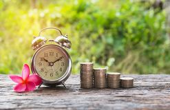 Coins in jar with money stack step growing money and alarm clock Stock Photo