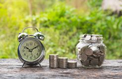 Coins in jar with money stack step growing money and alarm clock Royalty Free Stock Images