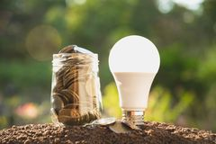 Coins in jar with money stack step growing money and light bulb,. Concept finance business and saving investment Stock Image