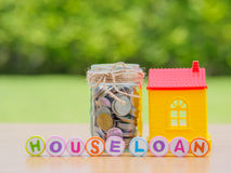 Coins in jar with red house. Saving for home concept Stock Photo
