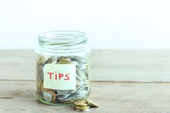 Coins in jar with Tips label. Coins in glass jar with Tips label. Money savings, tips and donation concept, copy space royalty free stock images