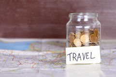 Coins in a jar with travel sign on a map against vintage brown w Stock Photo