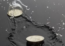 Coins jumping on water stock photo