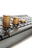 Coins on keyboard Stock Photography